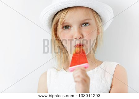 Little Caucasian Girl Eating Her Popsicle In White Dress And White Summer Hat Indoors. Sweet Tooth I