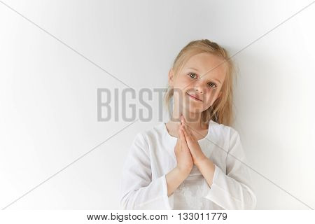 Portrait Of European Blond Kid Smiling And Folding Hands Like A Prayer. Her Total White Look And Cha