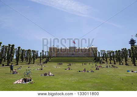 Frederiksberg, Denmark - June 5, 2016: People enjoying the sunshine in front of the castle in Frederiksberg park on a Sunday afternoon.