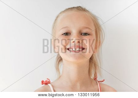 Close-up Portrait Of Blond European Little Girl Smiling With All Her Teeth. Happy Kid In Sunny After