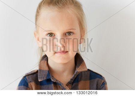Close Up Portrait Of Blond European Female Child. Little Kid With Green Eyes Staring At Camera In Mo