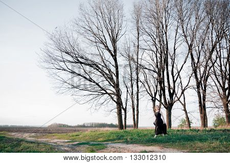 Sad and lonely woman looking for somebody in the field. Beautiful girl in black dress outdoors. meadow.