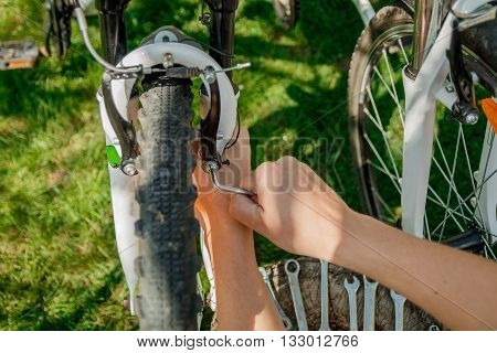 Fixing bicycle wheel with hands outdoor closeup