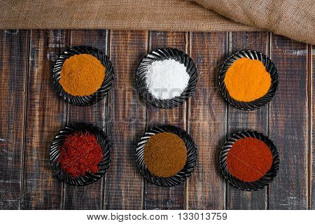 Spices in black ceramic plates on wooden background. Various spices selection. Six plates with different colorful spices near sackcloth top view.