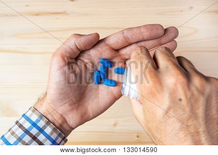 Top view pov of adult man taking blue pills selective focus