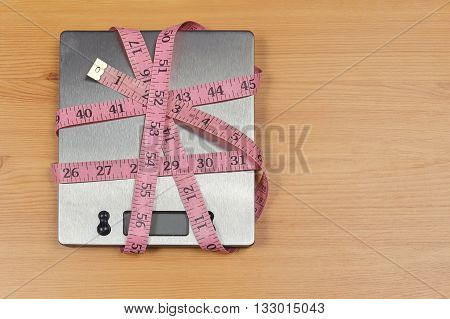 Digital kitchen scale wrapped inside tape measure for diet concept
