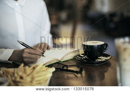 close up of a woman writing her notebook in a cafe