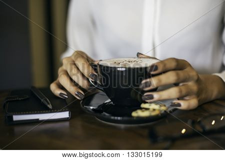 close up of a woman drinking coffee by a wooden table