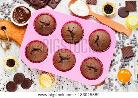 Homemade chocolate muffins on white table with ingredients. Baking food concept top view
