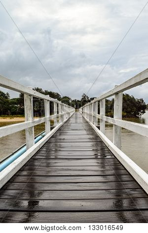 White timber pedestrian bridge crossing on an overcast and drizzly day - no people