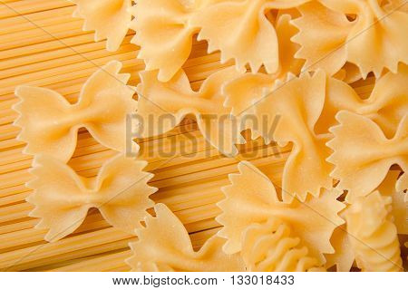Raw pasta background. Mixed dried pasta selection on black wooden background. Variety of types and shapes of Italian pasta.