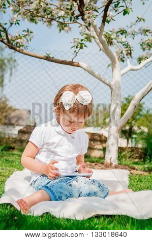 baby girl dressed in white polo and jeans barefoot sitting with tablet on the fur blanket in the park. Young girl getting into learning on her tablet