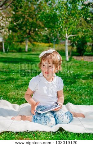 Little baby girl dressed in white polo and jeans barefoot sitting with tablet on the white fur blanket in the park with blossoming trees in the background.