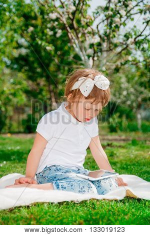 Little baby girl dressed in white polo and jeans barefoot sitting with tablet on the white fur blanket in park with blossoming trees in the background. Young girl getting into learning on tablet