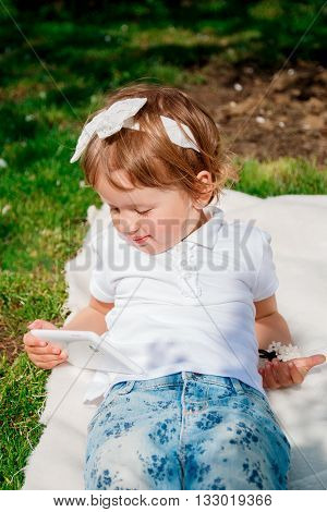 baby girl dressed in white polo and jeans barefoot lying on her back with tablet on the fur blanket in the park. Little girl playing on the tablet