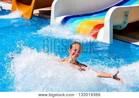 Child on water slide at aquapark and hands to side. There are two water slides with flowing water in aqua park. Summer swimming holiday. Outdoor.