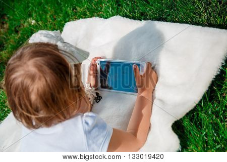 unrecognizable baby girl dressed in white polo and jeans barefoot lying with tablet on the fur blanket in the park. Little girl Using a Tablet closeup top view