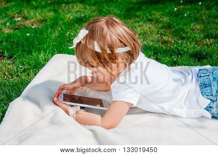 unrecognizable baby girl dressed in white polo and jeans lying with tablet on the blanket in the park. Little girl Using a Tablet closeup. kid hold tablet smartphone phone for playing and education.