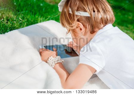 unrecognizable baby girl dressed in white polo and jeans barefoot lying with tablet on the fur blanket in the park. Little girl Using a Tablet closeup. kid's hold tablet smartphone phone for playing and education.