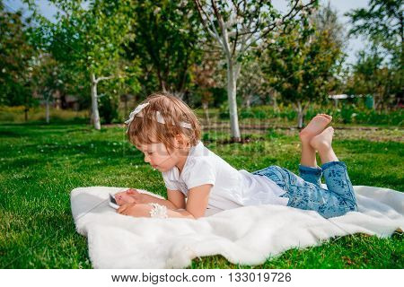 baby girl dressed in white polo and jeans barefoot lying with tablet on the fur blanket in the park. Little girl studies on the tablet