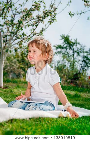 Little baby girl dressed in white polo and jeans barefoot sitting with tablet on the white fur cover in the park. Girl Using a Tablet.