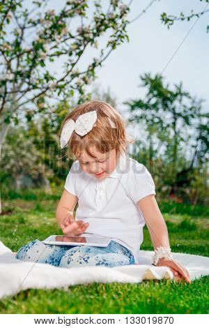 baby girl dressed in white polo and jeans barefoot sitting with tablet on the white fur cover in the park. Little girl play a game on tablet.