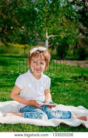 Little baby girl dressed in white polo and jeans barefoot sitting with tablet on the white fur cover in the park. Girl Using a Tablet. looking at the camera