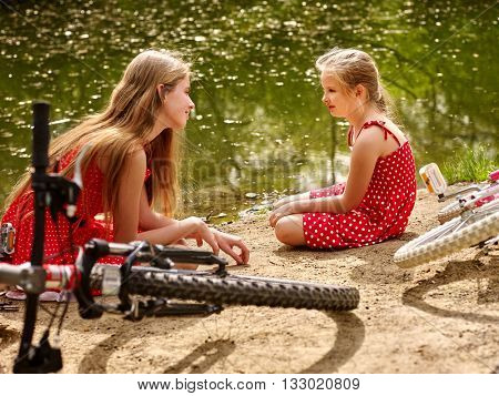 Bikes cycling family. Happy mother and daughter rides bicycle. Family have rest near water in park. Bicycles are on coast.