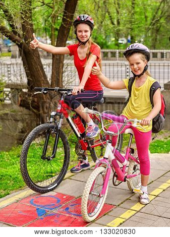 Bikes bicyclist girl. Girls wearing bicycle helmet with rucksack ciclyng bicycle show thumb up. Girls children cycling on yellow bike lane. Bike share program save money and time.