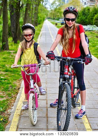 Bikes bicyclist girl. Girls wearing bicycle helmet and glass with rucksack ciclyng bicycle. Girls children cycling on yellow bike lane. Bike share program save money and time at city street.
