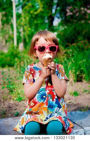 Cute and happy little girl in pink sunglasses sitting and eating ice cream outdoor. Yummy ice cream