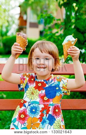 Cute and happy little girl raised above her head hands with two ice creams outside. Yummy ice cream