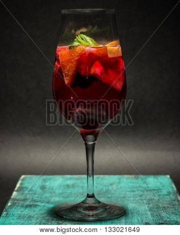 summer fruit cocktail in wine glass, lemonade on wooden board, sangria with pieces of orange, grapefruit, berries, closeup studio photo, dark background