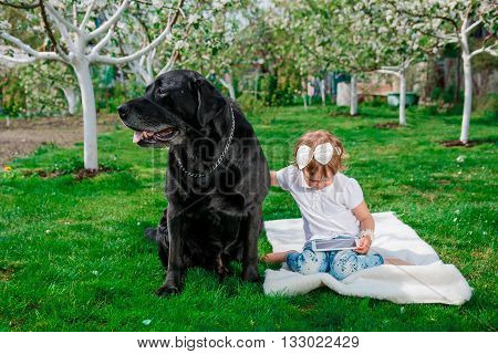 black labrador near Little baby girl using Tablet sitting on the white cover in the park .
