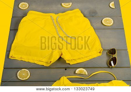 Beach Accessories On Wooden Background. Yellow Swim Shorts, Aviator Sunglasses, Lemon On Grey Wooden