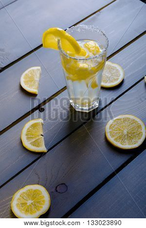 Lemonade With Fresh Lemon On Wooden Background. Lemonade Between Parts Of Lemons.