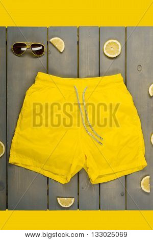 Yellow Swim Shorts, Aviator Sunglasses Between Parts Of Lemons On Grey Wooden Board. Man Beach Acces
