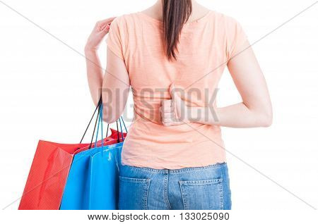 Female Holding Shopping Bags And Showing Thumb-up Behind Back