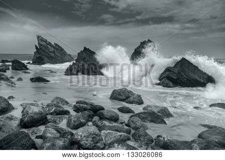 Black and White artistic Ocean beach landscape - Big waves breaking on the shore with rocks