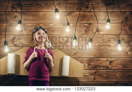 Little child girl plays astronaut. Child on the background of wooden wall. Child in an astronaut costume plays and dreams of becoming a spaceman.