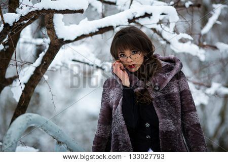 Sexy, beautiful, attractive girl, woman, teacher, student, businesswoman in luxury mink fur coat, with glasses, red lips, curly hair in snowy, cold, winter forest with trees in the snow. December. January. February