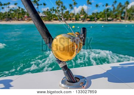 Boat fishing rods and closeup reel in front of tropical coastline