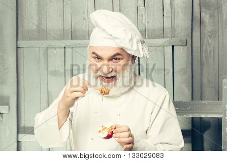 Bearded man cook in chef hat with apple and honey on wooden background