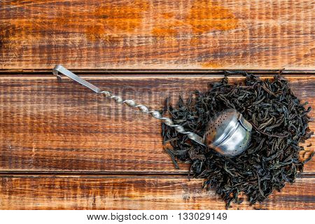 Vintage strainer with dry leaves of black tea on wooden background. Tea concept. Tea leaves. Top view. Closeup. Copy space