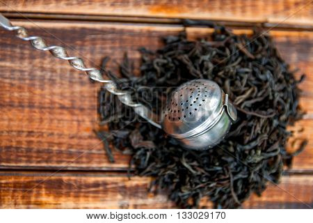 Vintage strainer with dry leaves of black tea on wooden background. Tea concept. Tea leaves. Top view. Closeup