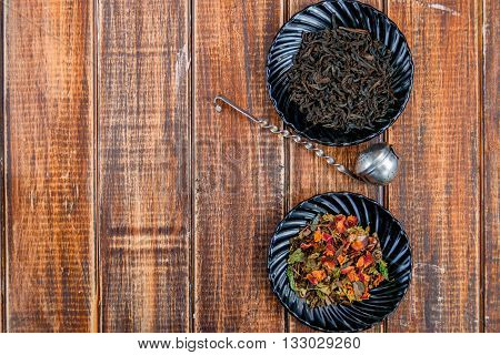 Different kinds of tea on plates on wooden background near vintage strainer. Assortment of dry tea. Tea concept. Tea leaves. Copy space. Top view. Frame