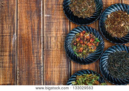 Different kinds of tea on plates on wooden background. Assortment of dry tea. Tea concept. Tea leaves. Top view. Copy space frame.