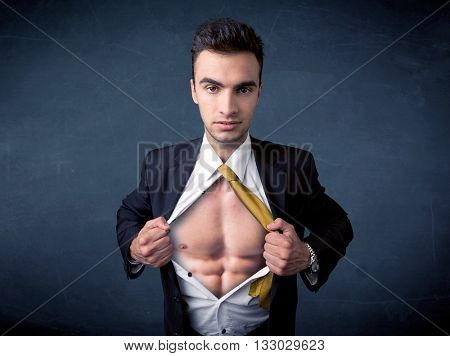 Businessman tearing off his shirt and showing muscular body concept on background