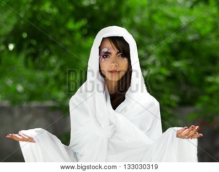 Cute girl as goddess. Beautiful, powerful, attractive, nice, pretty goddess, diva, queen, princess in white light soft cloth, textile with open arms stand in summer green park. Sunny diva, heroine in white cloak, cape, skicker, mantle. Fashionable model,