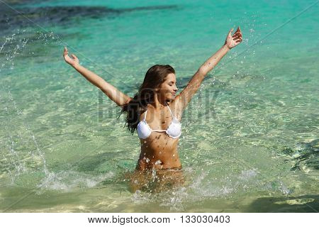 Young beautiful happy woman playing in blue water on a sunny day. Pretty girl enjoying vacation, sun and sea.
